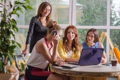 Un gruppo di togeather di lavoro della donna di affari graziosa quattro con il nuovo progetto startup facendo uso del computer po Fotografia Stock Libera da Diritti