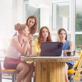 Un gruppo di togeather di lavoro della donna di affari graziosa quattro con il nuovo progetto startup facendo uso del computer po Immagini Stock