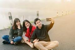 Un gruppo di tre amici asiatici che portano un maglione facendo uso di un telefono del selfie per prendere le immagini in un'attr fotografia stock libera da diritti