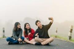 Un gruppo di tre amici asiatici che portano un maglione facendo uso di un telefono del selfie per prendere le immagini in un'attr fotografie stock