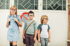 Un gruppo di tre bambini divertenti che indossano gli zainhi che cammina di nuovo alla scuola Immagini Stock