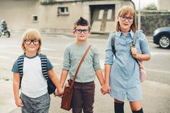 Un gruppo di tre bambini divertenti che indossano gli zainhi che cammina di nuovo alla scuola Fotografia Stock Libera da Diritti