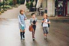 Un gruppo di tre bambini divertenti che indossano gli zainhi che cammina di nuovo alla scuola Immagine Stock