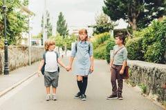 Un gruppo di tre bambini divertenti che indossano gli zainhi che cammina di nuovo alla scuola Fotografia Stock