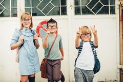 Un gruppo di tre bambini divertenti che indossano gli zainhi che cammina di nuovo alla scuola Fotografie Stock