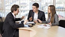 Un gruppo di tre genti che hanno discussione Immagini Stock