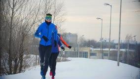 Un gruppo di tre giovani atleti che corrono tecnicamente nella foresta di inverno video d archivio