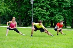 Un gruppo di tre giovani atleti che fanno allungando esercizio Fotografia Stock Libera da Diritti
