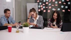 Un gruppo di tre giovani colleghe che si siedono nella tavola enorme bianca dell'ufficio moderno del sottotetto, esaminante i lor archivi video