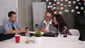 Un gruppo di tre giovani colleghe che si siedono nella tavola enorme bianca dell'ufficio moderno del sottotetto, esaminante il lo stock footage