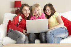 Un gruppo di tre ragazze che per mezzo del computer portatile nel paese Fotografia Stock