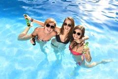 Un gruppo di tre ragazze felici che hanno bagno nella piscina t Immagine Stock