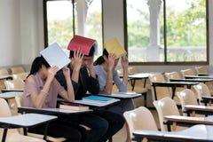 Un gruppo di tre studenti che per mezzo di una copertura prenota sulla testa nel Cl Fotografia Stock