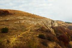 Un gruppo di tre viandanti che vanno sul percorso della traccia Una panoramica di una scalata di tre viaggiatori con zaino e sacc Fotografia Stock Libera da Diritti