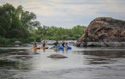 Un gruppo di turisti che trasportano sui catamarani lungo il fiume con le rive rocciose Rafting sul fotografia stock