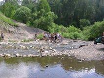 Un gruppo di turisti sulle biciclette fermate vicino al lago nelle montagne fotografia stock libera da diritti