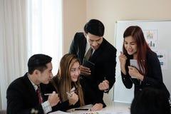Un gruppo di uomini di affari e le donne deliziano, felice in un mee di affari Immagine Stock