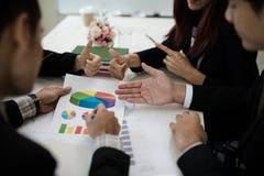 Un gruppo di uomini di affari e le donne stanno incontrando insieme per vedere il gr Fotografie Stock Libere da Diritti