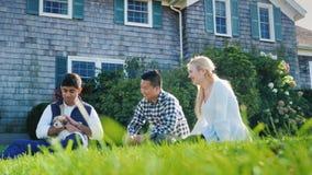 Un gruppo multi-etnico di amici sta riposando nel cortile, sedendosi sul prato inglese, giocante con un cucciolo archivi video