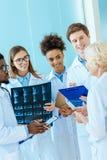 Un gruppo multirazziale di giovani interni medici che ascoltano un medico più anziano in a Immagine Stock Libera da Diritti