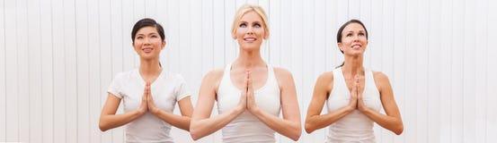 Un gruppo panoramico di tre belle donne che praticano yoga fotografia stock