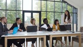 Un gruppo sicuro ed attraente di affari del gruppo di persone multiethnical sta tenendo una riunione d'affari ad una luce video d archivio