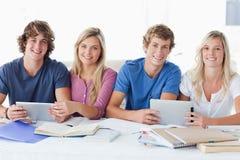 Un gruppo sorridente di studenti che esaminano la macchina fotografica Fotografia Stock