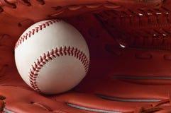 Un guante y una bola de béisbol en el fondo blanco. Foto de archivo