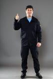 Un guardia de seguridad con un pulgar encima de la muestra Imagen de archivo libre de regalías