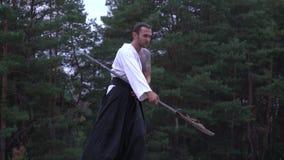 Un guerrero concentrado con un tatuaje en su hombro se convierte en una postura que lucha con una alabarda en sus manos almacen de video