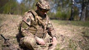 Un guerrero o un soldado militar vestido en la granada principal del camuflaje que estira o mina de las granadas y de las cuerdas almacen de video