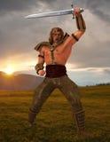 Un guerrier fier sur le champ à l'aube Image stock