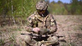 Un guerriero o un soldato militare vestito in cammuffamento con una sigaretta nella sua bocca, ha decollato il suo guanto ed ha a archivi video