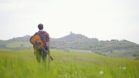Un guitariste de jeune homme marchant sur un pré vert clair - concept de déplacement clips vidéos