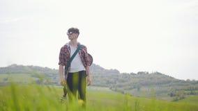 Un guitariste de jeune homme marchant sur un pré vert - concept de déplacement banque de vidéos