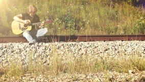 Un guitarrista de pelo largo que se sienta en el ferrocarril y jugar almacen de video