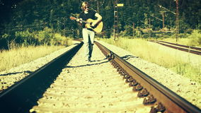 Un guitarrista zurdo camina a lo largo del ferrocarril y de los juegos almacen de metraje de vídeo