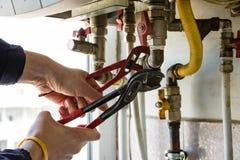 Un gur repara el filtro de la caldera de gas con las llaves Foto de archivo