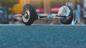 Un gyroboard su una strada affollata Un uomo si avvicina ad un gyroboard diritto, ottiene su e va archivi video