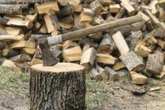 Un hacha se pegó en un frente del inicio de sesión de una pila de madera Fotos de archivo