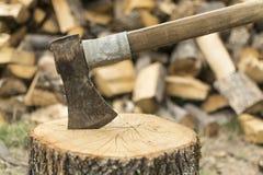 Un hacha se pegó en un frente del inicio de sesión de una pila de madera Imagen de archivo