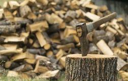 Un hacha se pegó en un frente del inicio de sesión de una pila de madera Imagen de archivo libre de regalías