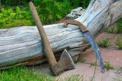 Un hacha, una sierra, un árbol que espera al equipo Imágenes de archivo libres de regalías