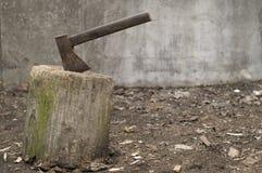 Un hacha vieja se pegó en un tronco de árbol stock de ilustración