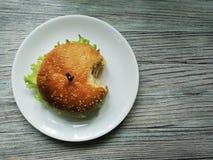 Un hamburger à moitié mangé d'un plat Images stock