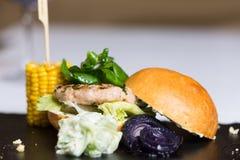Un hamburger di raduno è servito con formaggio e le verdure Immagine Stock