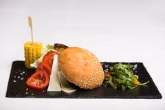 Un hamburger di raduno è servito con formaggio e le verdure Immagini Stock Libere da Diritti
