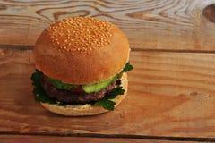 Un hamburger su fondo di legno Fotografia Stock Libera da Diritti