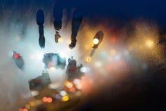 Un handprint su un vetro appannato, contro un fondo di una via di notte Immagine Stock