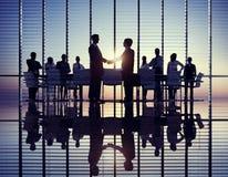 Un handshake di due uomini d'affari con i loro colleghi immagini stock